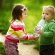 Boy and girl sharing bottle of water — Photo