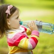 Little girl drinks mineral water — Stock Photo #17214767