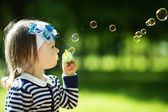 Little funny girl plays with bubbles — Stock Photo