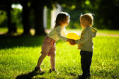 Chlapec a dívka si hraje s míčem — Stock fotografie