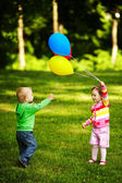 Girl and boy playing with balloons in park — Stock Photo