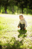 Little funny boy sitting in grass — Stock Photo
