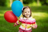 Little girl plays with balloons — Stock Photo