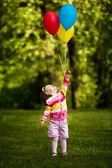 Petite fille drôle joue avec des ballons dans le parc — Photo