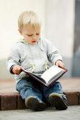 Little boy reads a book — Stock Photo