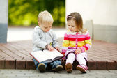 Cute boy and girl reading a book — Stock Photo