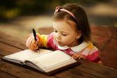 Een klein meisje leren schrijven — Stockfoto