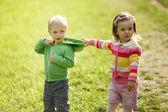 A menina puxa o capuz do menino — Fotografia Stock