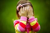Baby speelt verstoppertje verbergen gezicht — Stockfoto