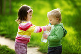 Boy and girl sharing bottle of water — Stock Photo