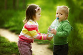 Boy and girl sharing bottle of water — Stok fotoğraf
