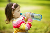 Little girl drinks mineral water — Stok fotoğraf