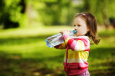Little girl drinks mineral water — 图库照片