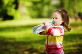 Petite fille boit de l'eau minérale — Photo