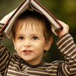 Boy with book on his head — Stock Photo
