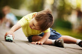 Little boy plays with toy car — Stok fotoğraf