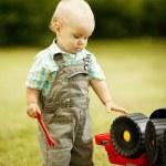 Постер, плакат: Little boy repairs toy car