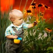 Little boy with a watering can check the quality of flowers — Stock Photo #17696239