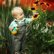 Little boy with a watering can check the quality of flowers — Stock Photo