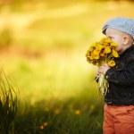 Постер, плакат: Cute little boy with dandelions