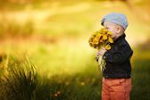 Cute little boy with dandelions — Stock fotografie