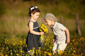 Cute boy and girl on summer field — Stock Photo