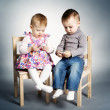 Little boy and girl playing with mobile phones — Stock Photo