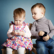 Stock Photo: Little boy and girl playing with mobile phones