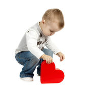 Cute little boy with red heart — Stock Photo