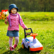 Little girl with toy car and flowers — Stock Photo