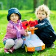 Boy and girl in park with toy car — Stock Photo