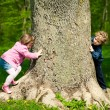 Photo: Girl and boy playing hide and seek