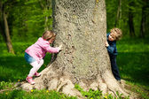 Girl and boy playing hide and seek — Stock Photo