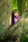 Little girl on big tree — Stock Photo