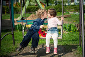 Boy and girl on the swings — Stock Photo