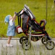 Little funny girl with baby carriage - Stock Photo