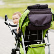 Little funny girl with baby carriage — Stockfoto