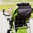 Little funny girl with baby carriage — Foto Stock