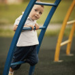 Little boy plays on playground - Stock Photo