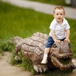 Little boy on a wooden crocodile — Stock Photo #23351356