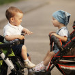 Boy and girl in baby carriages — Stock Photo