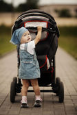 Little funny girl with baby carriage — Stock Photo
