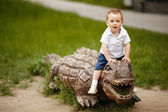 Little boy on a wooden crocodile — Stock Photo