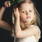 Little girl combing her long beautiful hair — Stock Photo