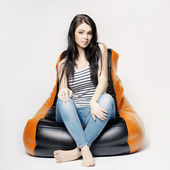 Beautiful brunette on bean bag — Stock Photo