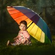 Little girl with a rainbow umbrella in park — Stock Photo #27885185