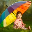 Little girl with rainbow umbrellin park — Stock Photo #27885193