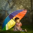 Little girl with a rainbow umbrella in park — Stock Photo #27885235