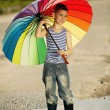 Little girl with a rainbow umbrella in park — Stock Photo