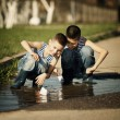 Little boy plays with paper boats in puddle — Stock Photo